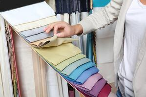 stock-photo-young-woman-choosing-fabric-for-new-curtains-in-shop-749206216