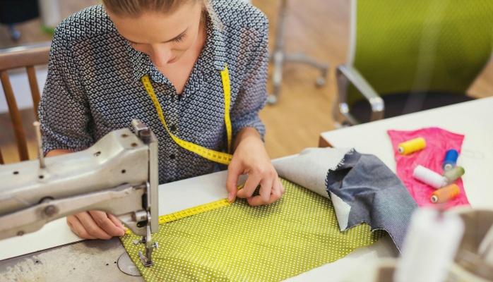 woman sewing green fabric